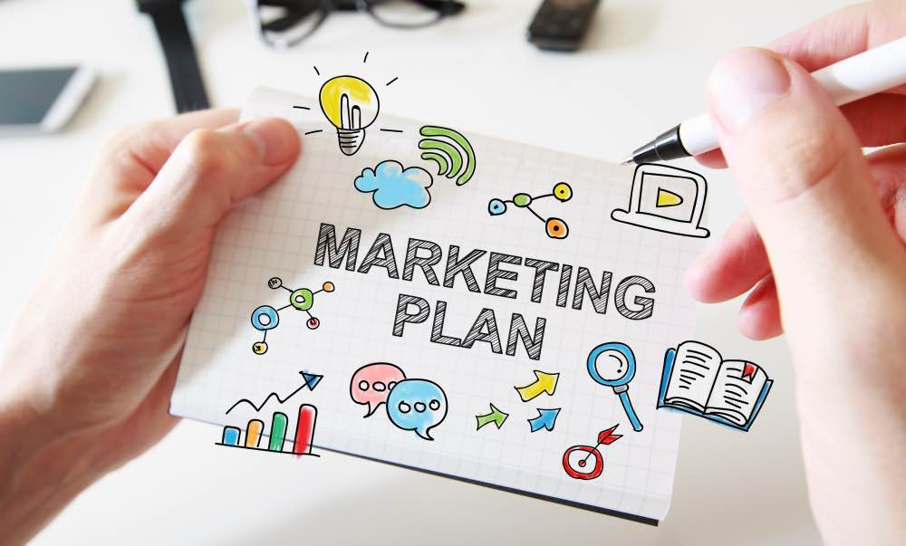 Mans hand drawing Marketing Plan concept on white notebook